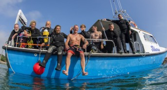 Jane-Morgan-Group-Topside-UK-Group-of-divers-on-a-boat-posing-for-a-photograph-looking-to-camera.jpg